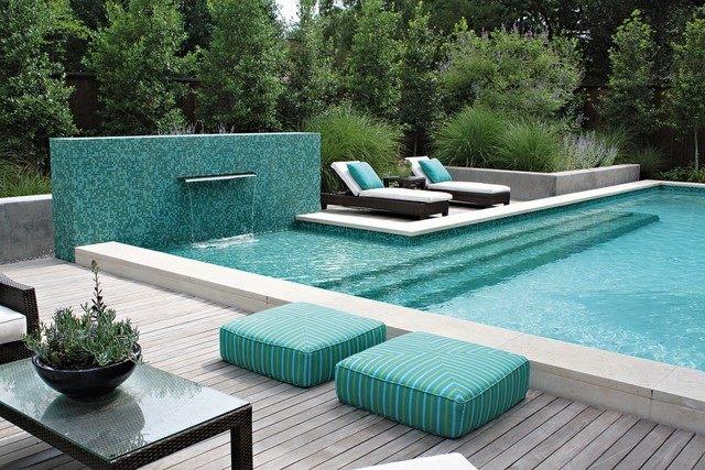 deck negro tumbonas jardin mosaico cascada