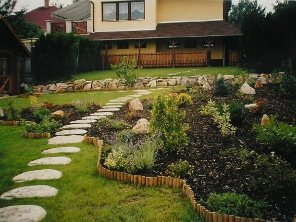 senda piedras redondas césped plantas