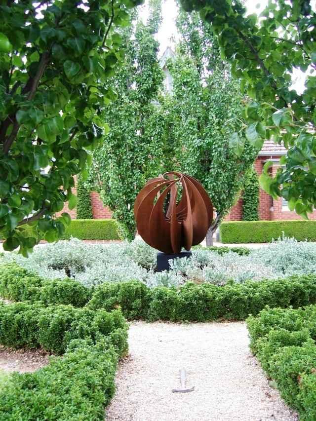 esfera acero camino grava arboles escultura