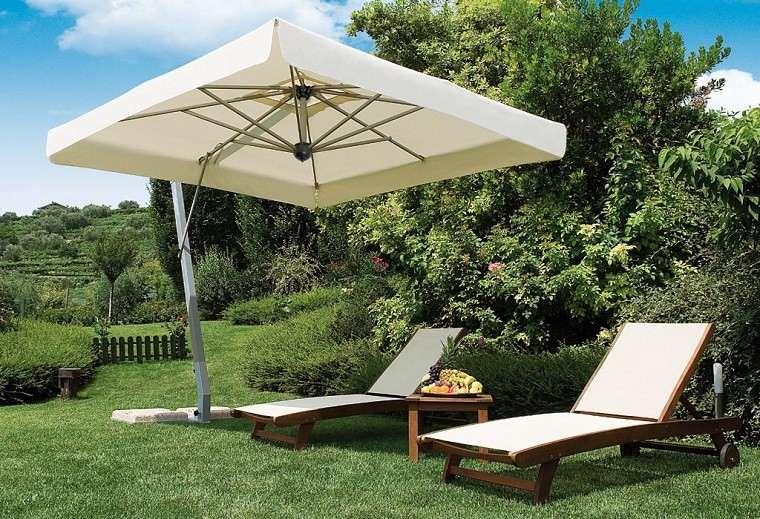estupenda sombrilla dos tumbonas jardin