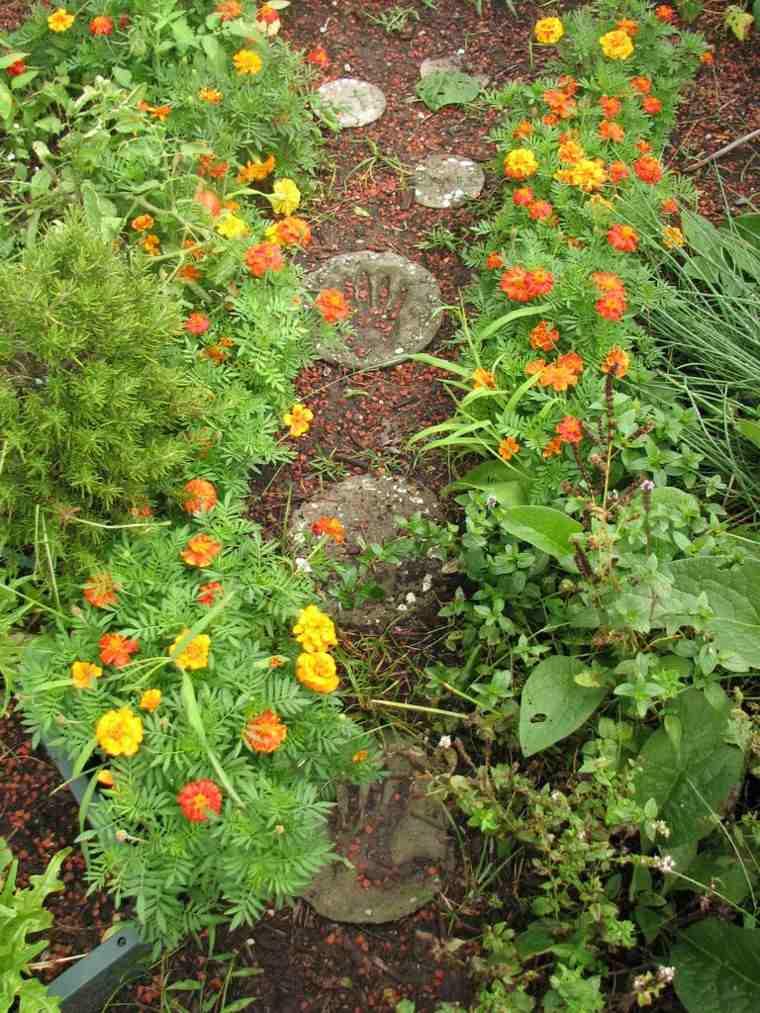 manos hormigon sendero flores marcado