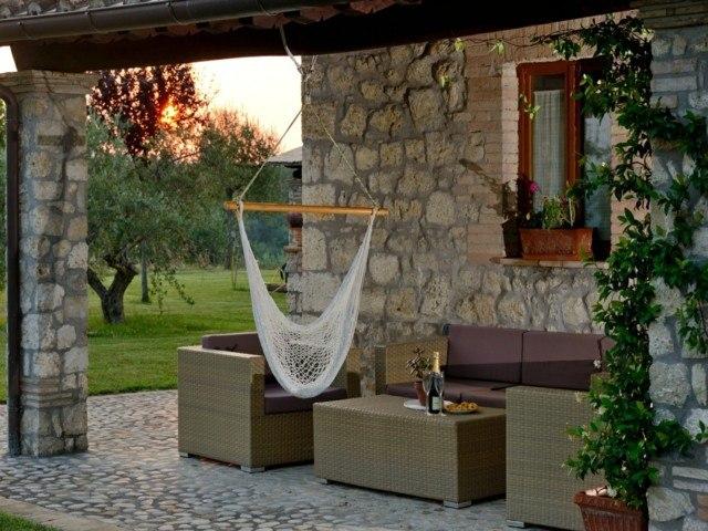 muebles terraza columnas piedra pared columpio
