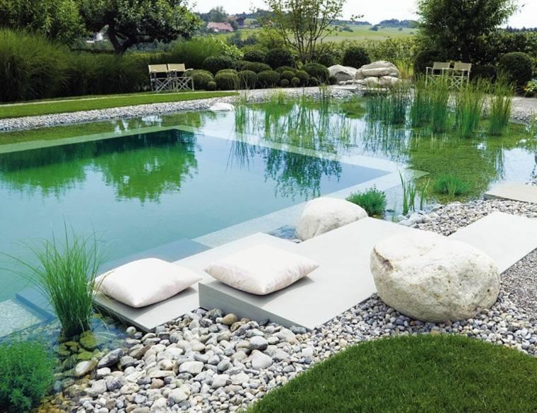 piscina natural cojines blancos piedras