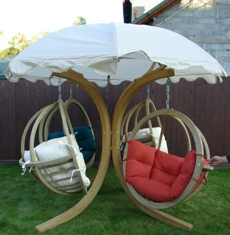 sillones colgantes de jardín varios cojines colores sombrilla blanca