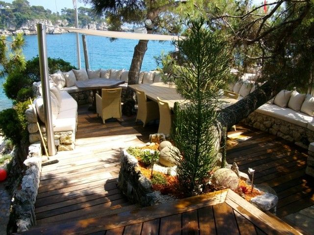 terraza amplia suelo madera banco piedra idea cojines