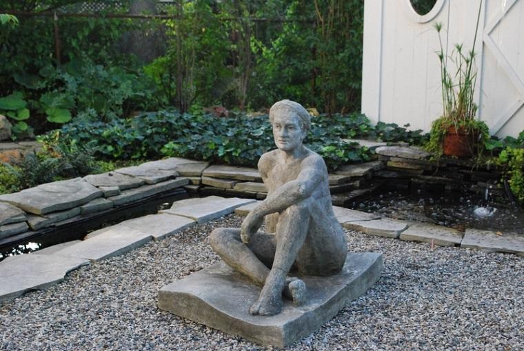 estatua mujer sentada grava piedras