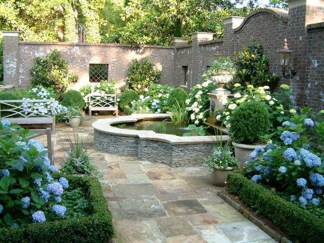 fuente jardin flores azules muro