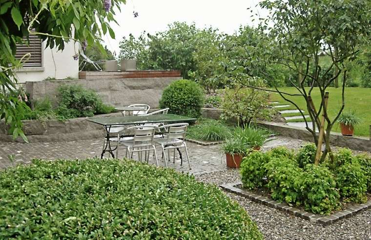 jardin muro hormigon dos niveles mesa sillas ideas