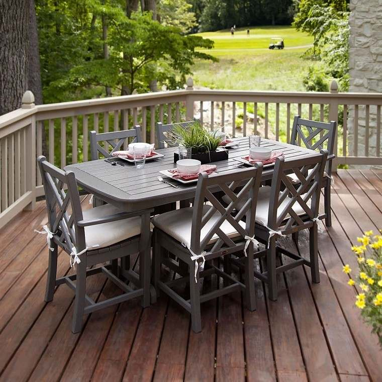 mesa madera sillas terraza flores jardin