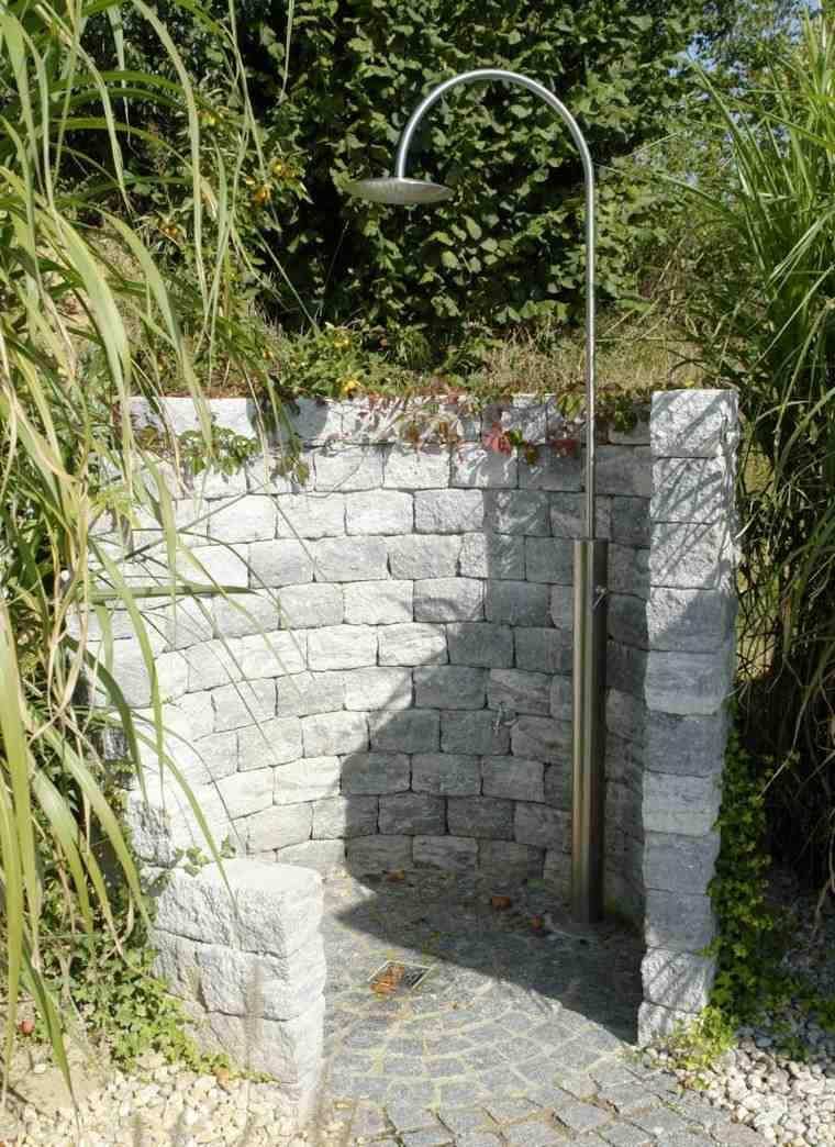 plato ducha rodeado muro piedras
