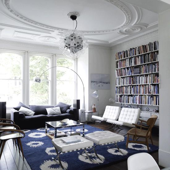 salon estilo moderno estanterias libros butacas cuero blanco