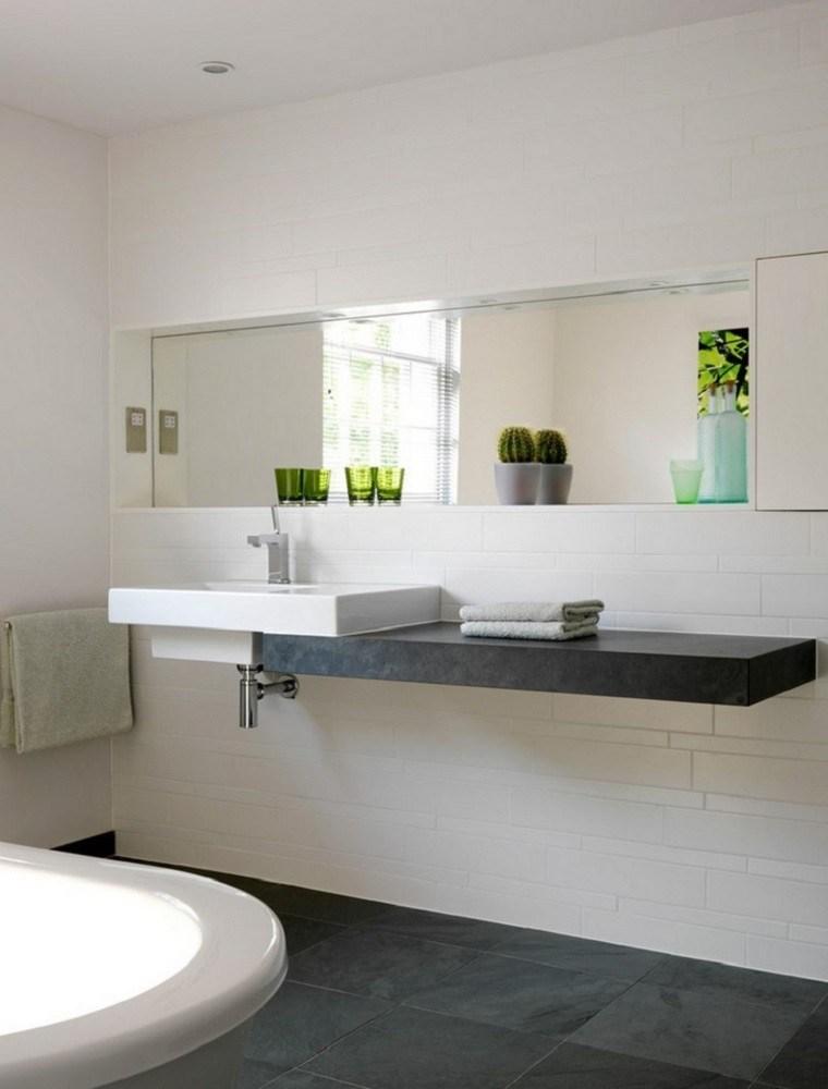 Baños Minimalistas De Lujo:Lavabo de granito y espejo grande en el baño al estilo minimalista