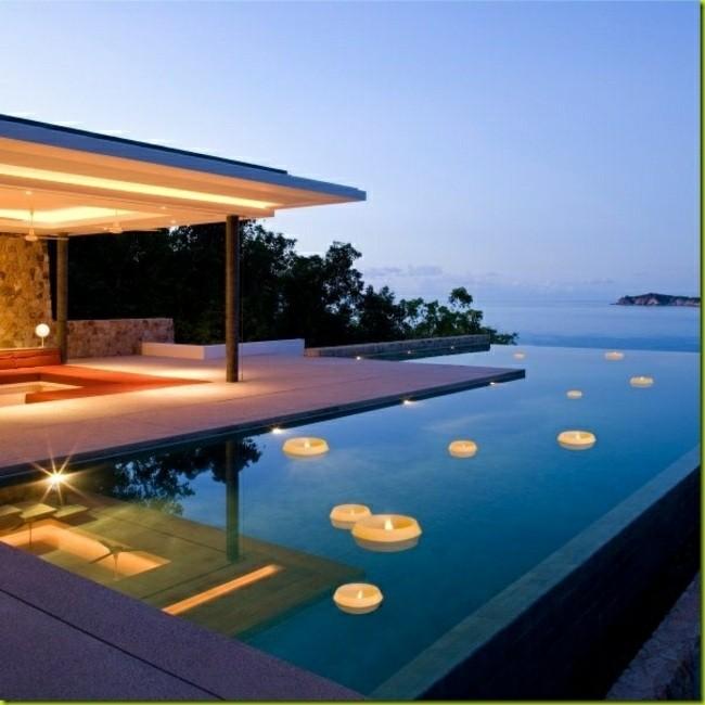 luces velas flotando piscina atardecer
