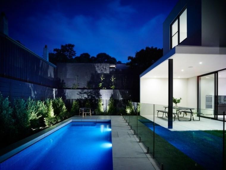 piscina iluminada noche mesa negra bancos ideas