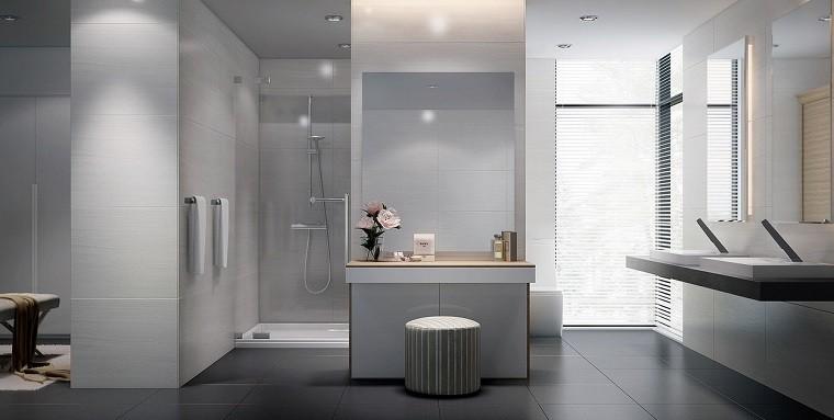 Baños Grises Modernos:Baño con suelo de madera y losas grises y blancas en la pared