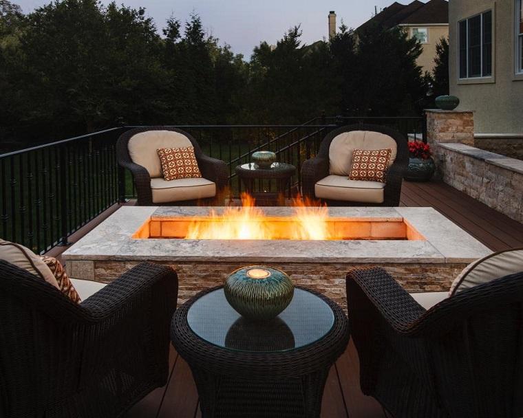 cuatro sillones rattan rodean lugar fuego terraza ideas