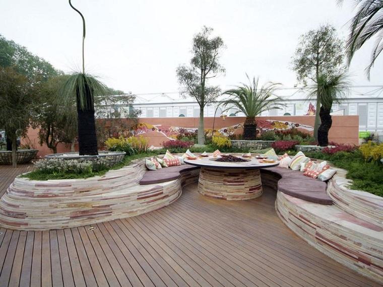 jardin moderno bancos piedra lugar fuego cojines colores ideas