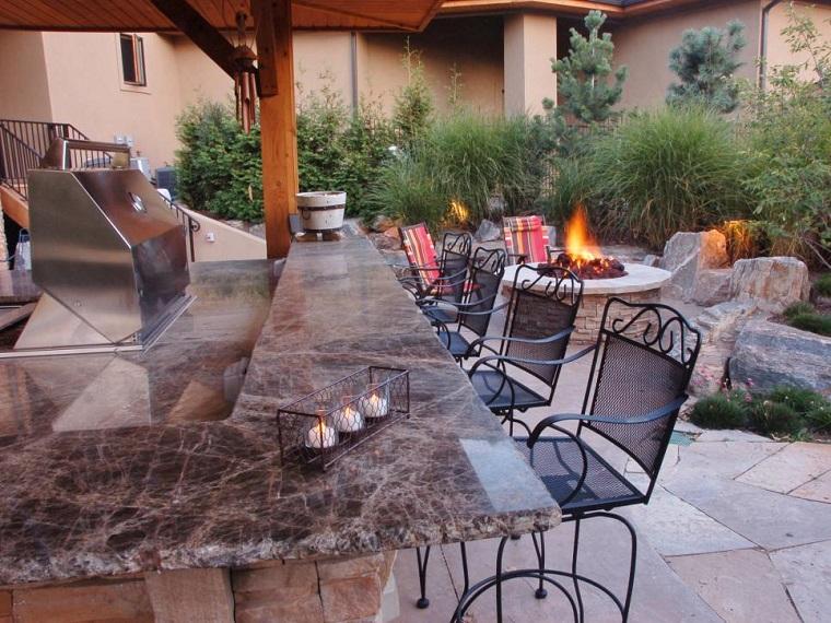Pozo o plato de fuego y muebles modernos en el jard n for Cocina exterior jardin