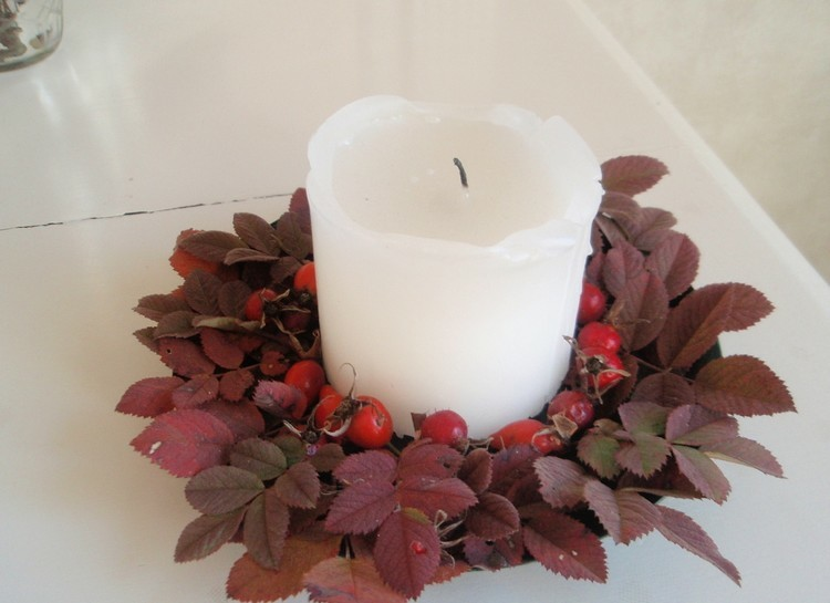 white candle decorated dry leaves