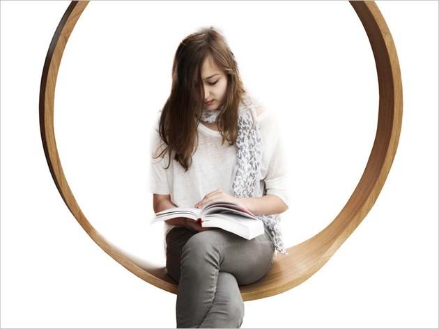 niña leyendo columpio madera