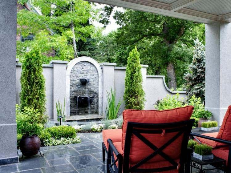 fuente agua pared sillones rojos jardin ideas