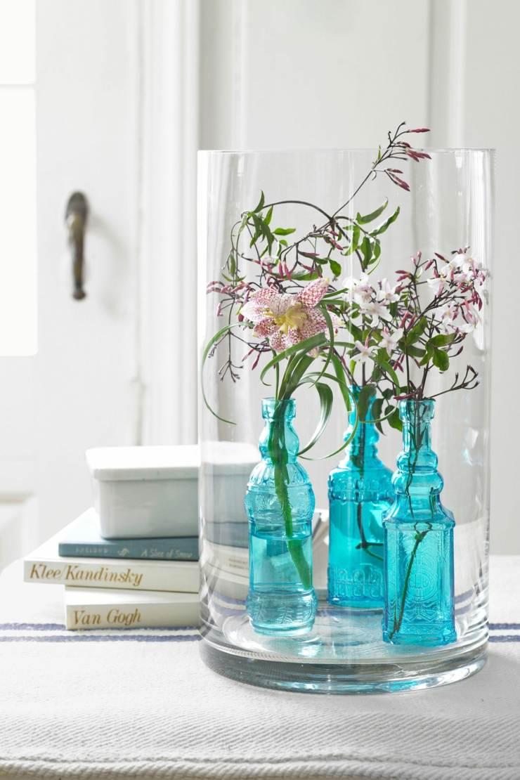 arreglos florales pocos tallos jazmín dispuestos botellas azules vintage pieza central elegante especial ideas