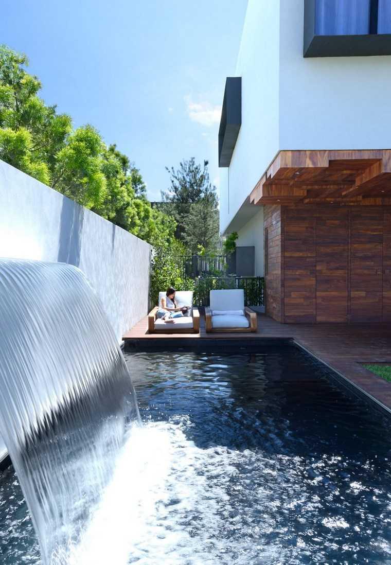 fotos jardins piscinas:Fotos de piscinas con fuentes decorativas y sillones de madera en el
