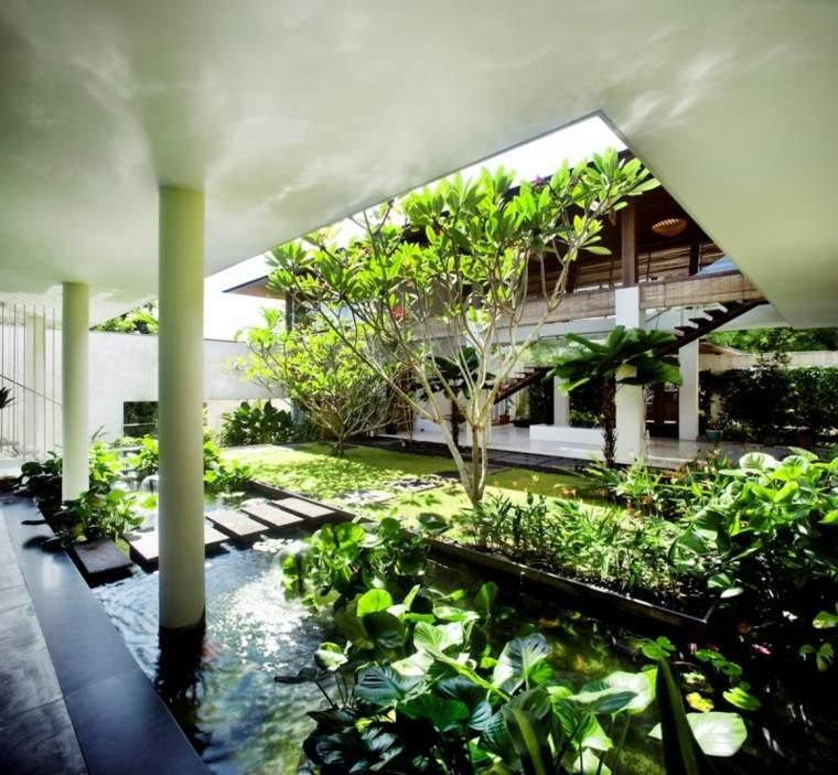 Un jardín con diseño tropical con muchas plantas y estanque moderno