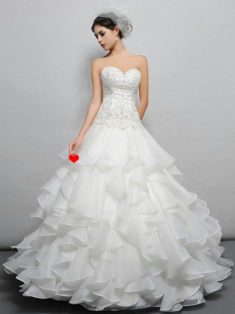 unos vestidos para novia ajustados hasta los muslos con una cola con mucho volumen