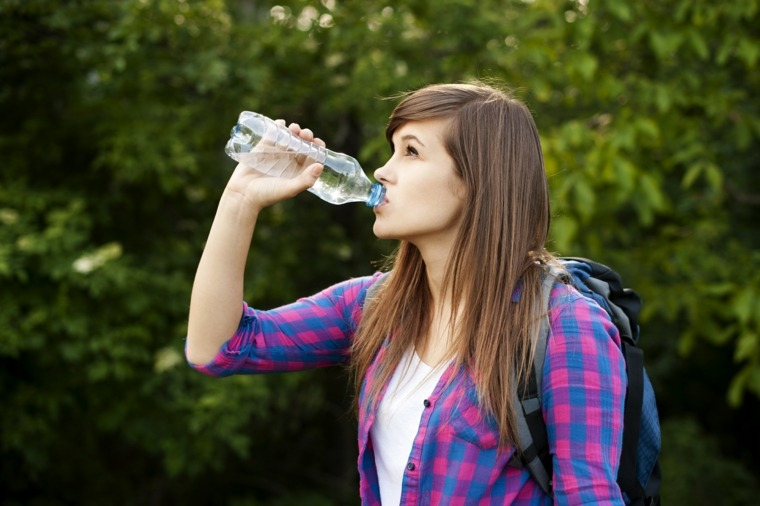 chica-tomando-agua-botella-plastico