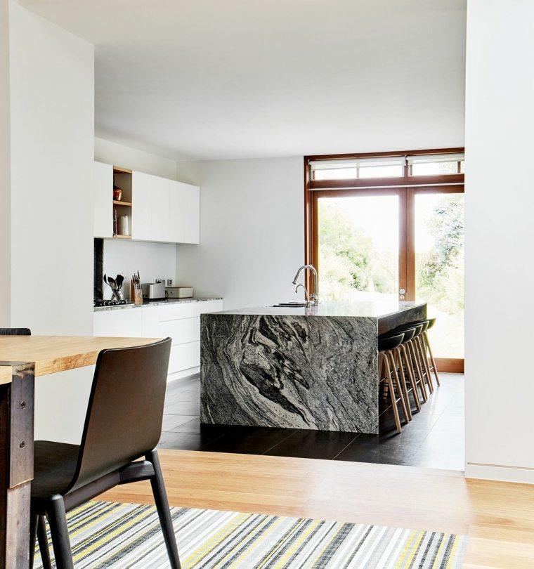 Una estupenda isla de cocina de mármol negro se muestra como el punto focal
