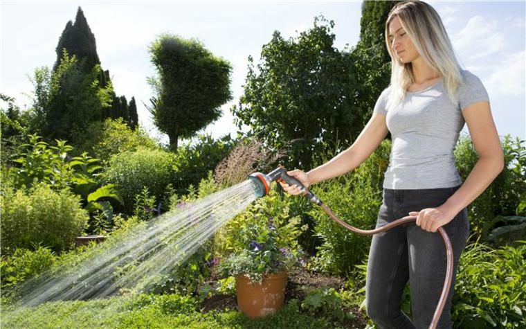 mujer regando el jardín