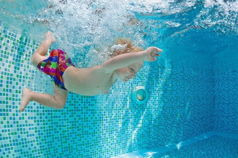 Niño chapoteando en la piscina
