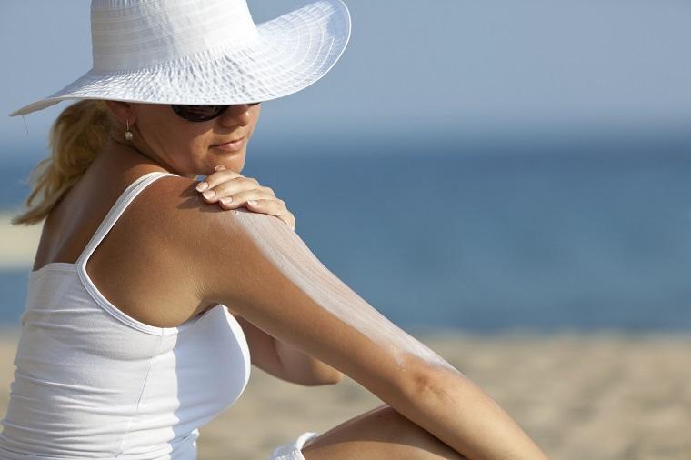mujer aplicando capa de locion protectora contra el sol