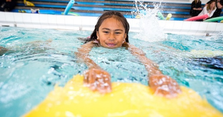 Niña con su tabla de nado