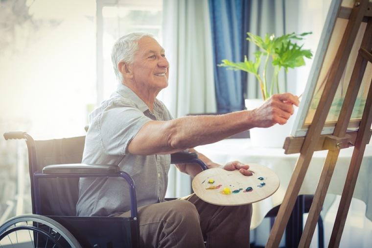 señor pintando alegre en su casa